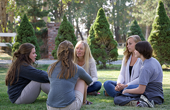 Students sitting on a lawn with a therapist at a boarding school for at risk girls