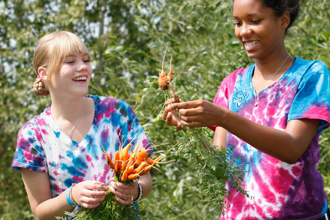 Girls harvesting carrots as experiential learning at a boarding school
