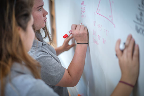 Girls working out problems on a whiteboard in the classroom