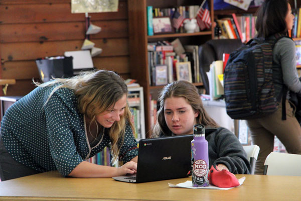 A boarding school teacher helping a student at her computer