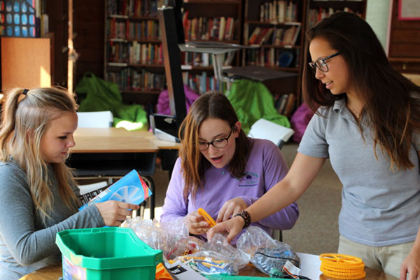 girls unpacking a STEM project in a boarding school classroom